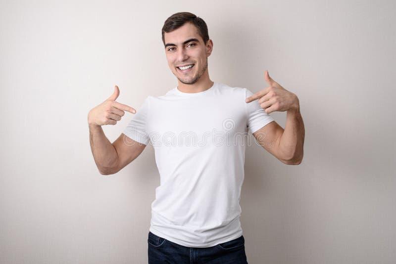 Το πορτρέτο του χαμογελώντας όμορφου νεαρού άνδρα σε μια άσπρη κενή μπλούζα την παρουσιάζει με τα δάχτυλά του, θέση για το σχέδιο στοκ εικόνα με δικαίωμα ελεύθερης χρήσης
