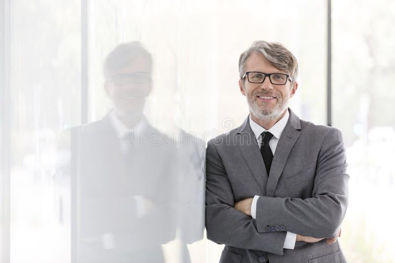Το πορτρέτο του χαμογελώντας ώριμου επιχειρηματία με τα όπλα διέσχισε την κλίση στον τοίχο στο γραφείο στοκ φωτογραφία με δικαίωμα ελεύθερης χρήσης