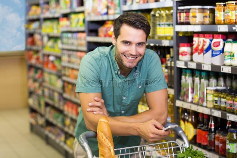 Το πορτρέτο του χαμογελώντας ατόμου αγοράζει τα τρόφιμα και χρησιμοποίηση του smartphone του στοκ φωτογραφία με δικαίωμα ελεύθερης χρήσης