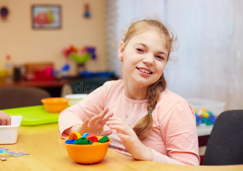 Το πορτρέτο του χαριτωμένου ευτυχούς κοριτσιού με ειδικές ανάγκες αναπτύσσει τις λεπτές δεξιότητες μηχανών στο κέντρο αποκατάστασ στοκ εικόνα