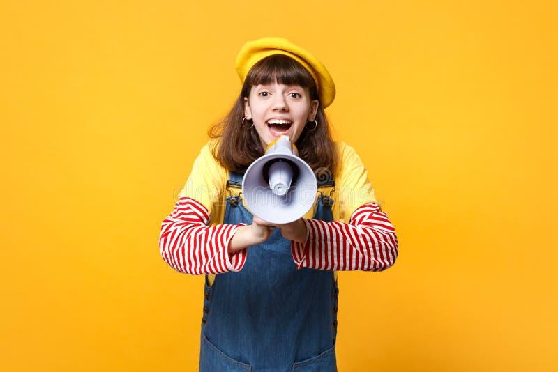 Το πορτρέτο του χαρούμενου όμορφου εφήβου κοριτσιών γαλλικό beret, τζιν sundress κραυγάζει megaphone που απομονώνεται στον κίτριν στοκ εικόνες