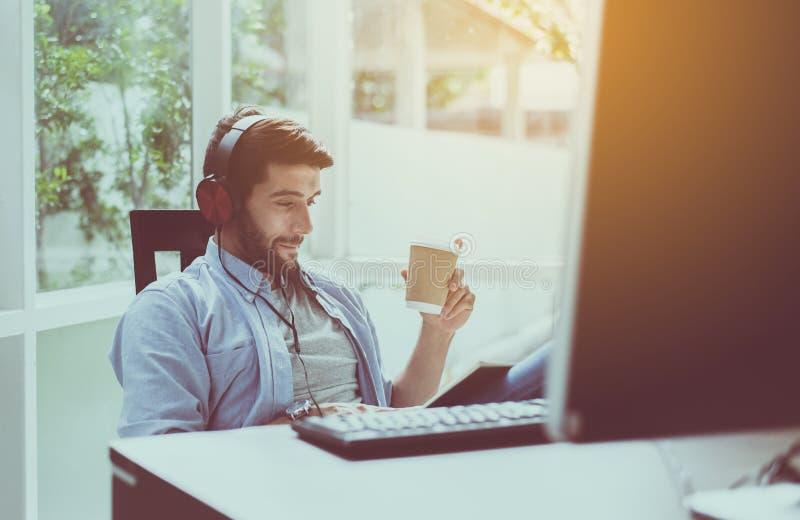 Το πορτρέτο του όμορφου ατόμου με τη γενειάδα που πίνει τον καυτό καφέ και που ακούει τη μουσική on-line στο σύγχρονο σπίτι, ευτυ στοκ φωτογραφία