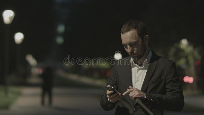 Το πορτρέτο του όμορφου ενήλικου επιχειρησιακού ατόμου επικοινωνεί τηλεφωνικώς στην καλή διάθεση, στεμένος στην οδό πόλεων, την ε στοκ εικόνες