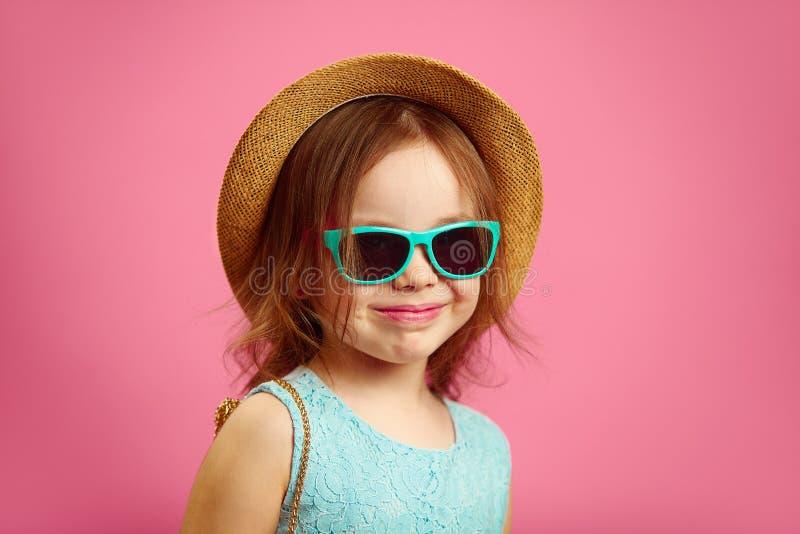 Το πορτρέτο του όμορφου μικρού κοριτσιού με το καπέλο αχύρου και τα γυαλιά ηλίου, φορούν το μπλε φόρεμα, στέκονται στο ροζ που απ στοκ φωτογραφία με δικαίωμα ελεύθερης χρήσης