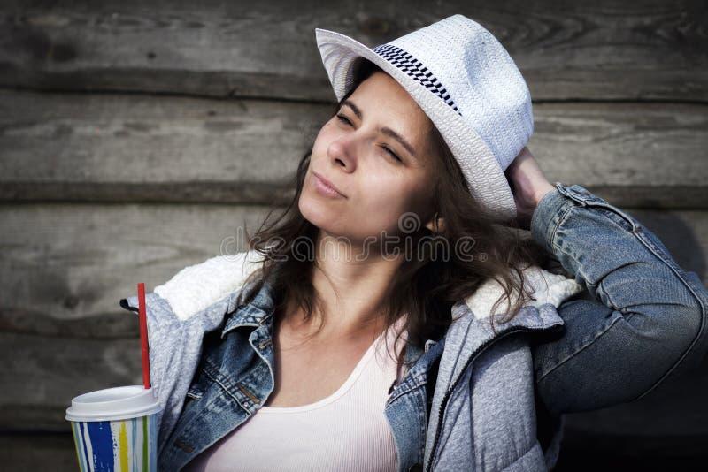 Το πορτρέτο του όμορφου χαριτωμένου ελκυστικού κοριτσιού στο σακάκι καπέλων και τζιν κρατά το δροσερό ποτό στο ποτήρι στο κλίμα τ στοκ φωτογραφία