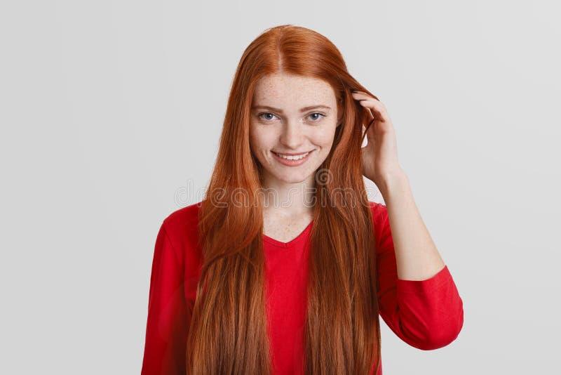 Το πορτρέτο του redhead νέου θηλυκού με μακρυμάλλη, έχει το φακιδοπρόσωπο πρόσωπο, ευχάριστο χαμόγελο, τρίχα αφών, πέρα από το άσ στοκ εικόνα με δικαίωμα ελεύθερης χρήσης