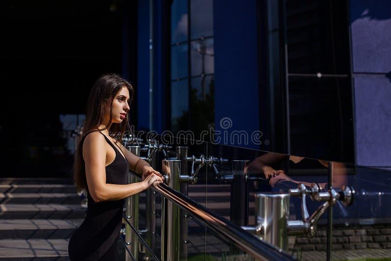 Το πορτρέτο τρόπου ζωής του όμορφου κοριτσιού με το makeup και τη μακροχρόνια τρίχα brunette φορά το μαύρο φόρεμα στην οδό στοκ εικόνες