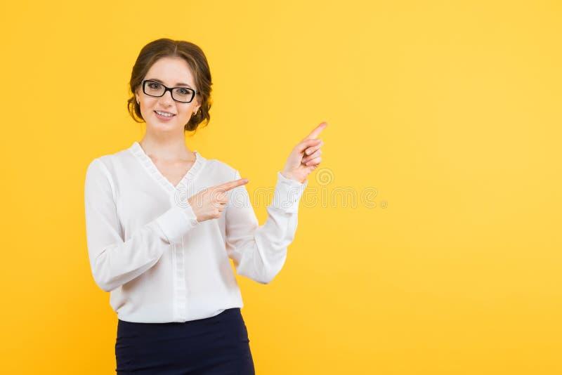 Το πορτρέτο των βέβαιων όμορφων νεολαιών που χαμογελούν την ευτυχή επιχειρησιακή γυναίκα παρουσιάζει στο blankarea στο κίτρινο υπ στοκ φωτογραφία με δικαίωμα ελεύθερης χρήσης