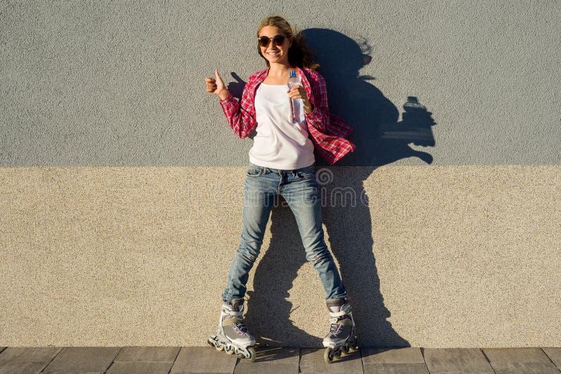 Το πορτρέτο των νεολαιών δροσίζει το χαμογελώντας κορίτσι που πεταλώνεται στα rollerblades, holdin στοκ φωτογραφία
