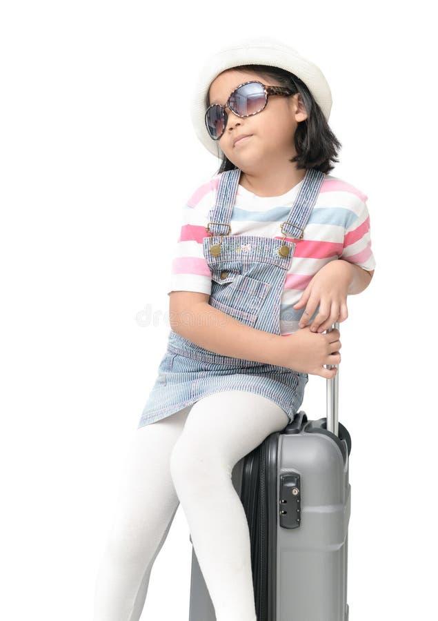 Το πορτρέτο των χαριτωμένων ασιατικών γυαλιών ηλίου ένδυσης κοριτσιών και κάθεται στη βαλίτσα στοκ φωτογραφία με δικαίωμα ελεύθερης χρήσης