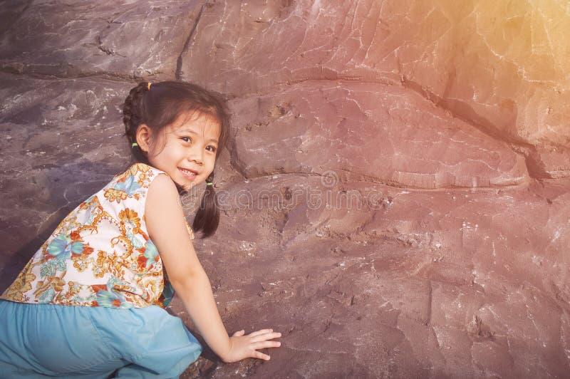 Το πορτρέτο χαριτωμένο λίγο ασιατικό ταϊλανδικό κορίτσι αναρριχείται σε έναν απότομο βράχο στοκ εικόνα