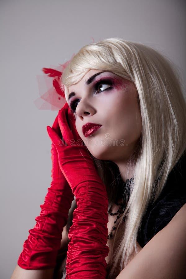 Το πορτρέτο cabaret της γυναίκας με το κόκκινο ακτινοβολεί makeup στοκ φωτογραφία