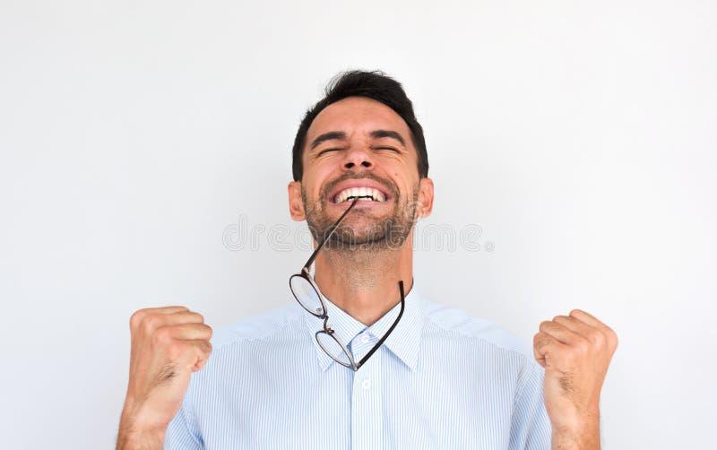 Το πορτρέτο Horziontal του ευτυχούς αξύριστου νέου αρσενικού νικητών σφίγγει τις πυγμές και γιορτάζει τη νίκη του, με τα θεάματα  στοκ εικόνα