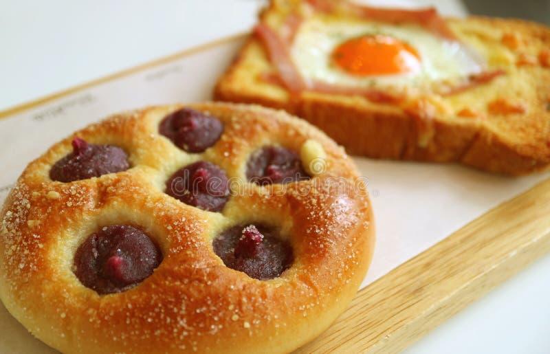 Το πορφυρό κουλούρι κρέμας γλυκών πατατών κινηματογραφήσεων σε πρώτο πλάνο με το μουτζουρωμένο αυγό και το ζαμπόν ψήνουν στο υπόβ στοκ εικόνες