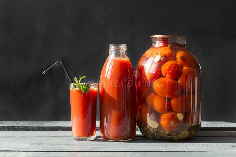 Το ποτήρι του χυμού ντοματών με τη μέντα και του αχύρου, χυμός ντοματών σε ένα μπουκάλι, κονσερβοποίησε τις ντομάτες σε ένα βάζο στοκ εικόνα