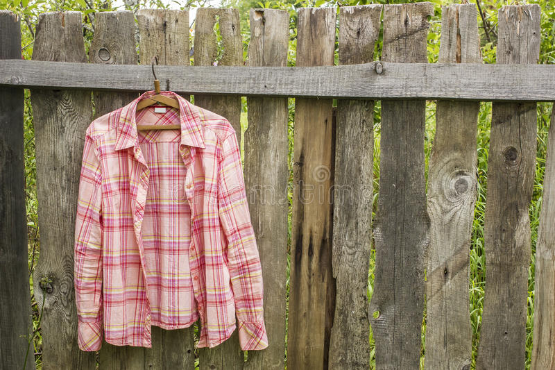 Το πουκάμισο κρεμά το α στην κρεμάστρα στον παλαιό φράκτη από τους πίνακες σε ένα villag στοκ εικόνα με δικαίωμα ελεύθερης χρήσης