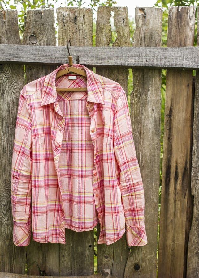 Το πουκάμισο κρεμά το α στην κρεμάστρα στον παλαιό φράκτη από τους πίνακες σε ένα villag στοκ εικόνα