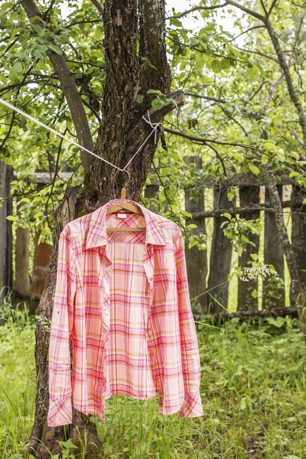 Το πουκάμισο κρεμά το α στην κρεμάστρα στο σχοινί ενάντια στο σκηνικό παλαιού στοκ φωτογραφίες με δικαίωμα ελεύθερης χρήσης