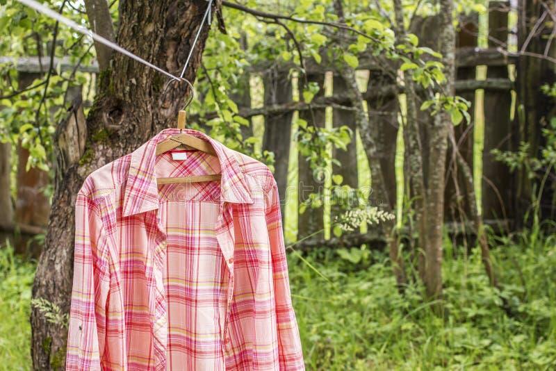 Το πουκάμισο κρεμά το α στην κρεμάστρα στο σχοινί ενάντια στο σκηνικό παλαιού στοκ φωτογραφία