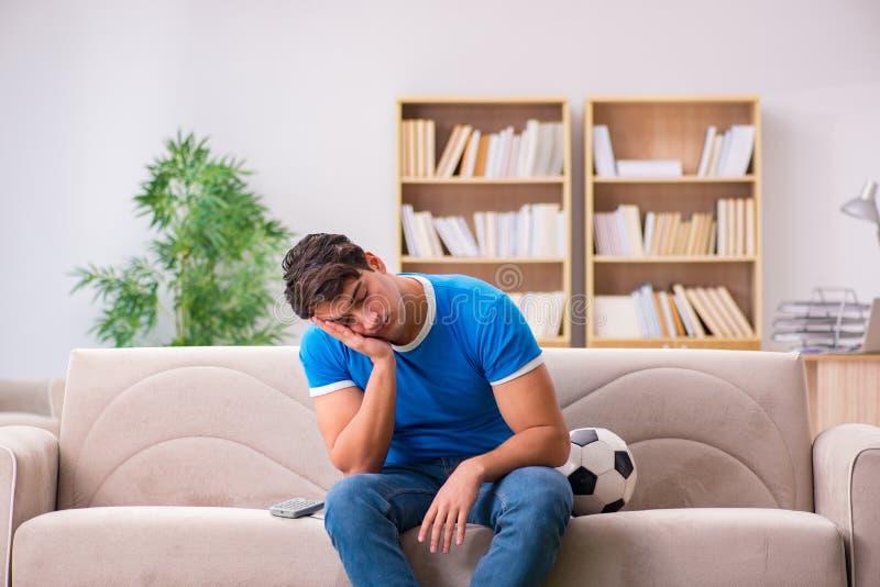 Το ποδόσφαιρο προσοχής ατόμων που κάθεται στο σπίτι στον καναπέ στοκ εικόνες
