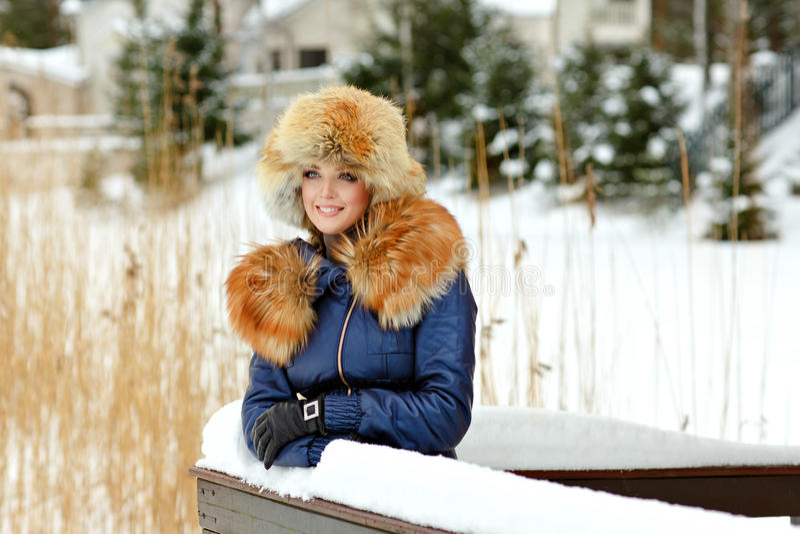 Το πολύ όμορφο κορίτσι glamor σε ένα καπέλο γουνών και ένα κόκκινο περιλαίμιο χαμογελά στοκ φωτογραφίες