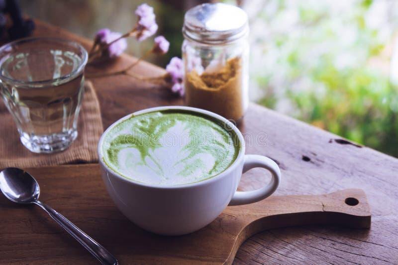 Το πράσινο άσπρο φλυτζάνι ποτών τσαγιού καυτό latte στο ξύλινο επιτραπέζιο άρωμα χαλαρώνει το Tj στοκ εικόνες