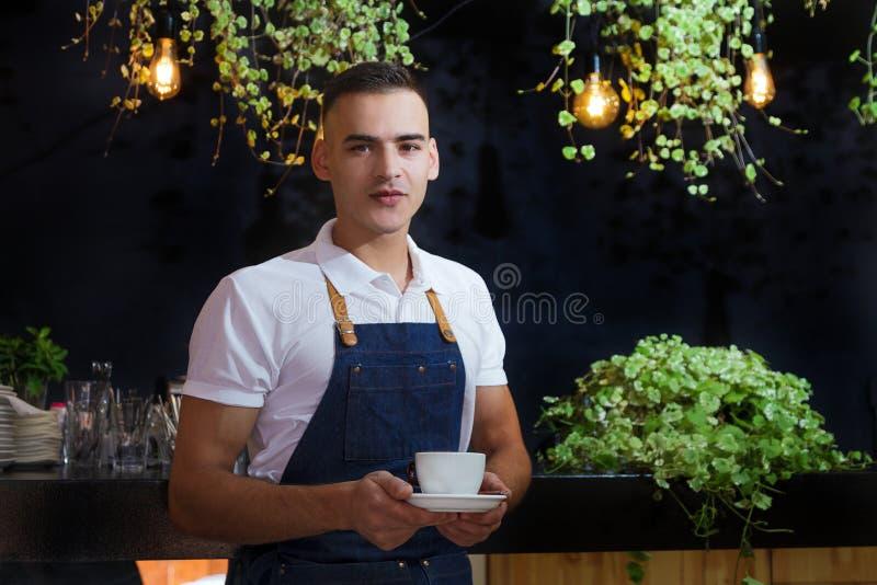 Το πράσινο λευκό σερβιτόρων αφήνει στο πορτρέτο φλυτζανιών καφέ τη νέα αρσενική ποδιά καφέδων πελατών καφέ υπηρεσιών barista στοκ εικόνα με δικαίωμα ελεύθερης χρήσης