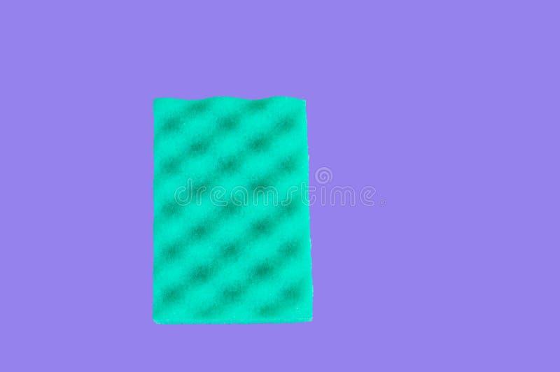 Το πράσινο σφουγγάρι για τον καθαρισμό, που απομονώθηκε στο πορφυρό υπ στοκ εικόνα