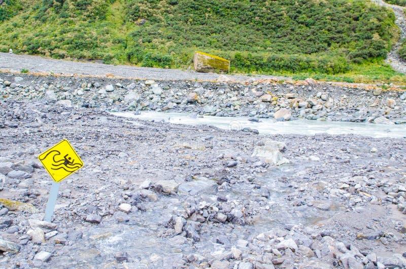 Το προειδοποιητικό σημάδι για τη λάμψη που πλημμυρίζει τα μεγάλα παλιρροιακά κύματα κοντά στο βουνό χιονιού στοκ φωτογραφία με δικαίωμα ελεύθερης χρήσης