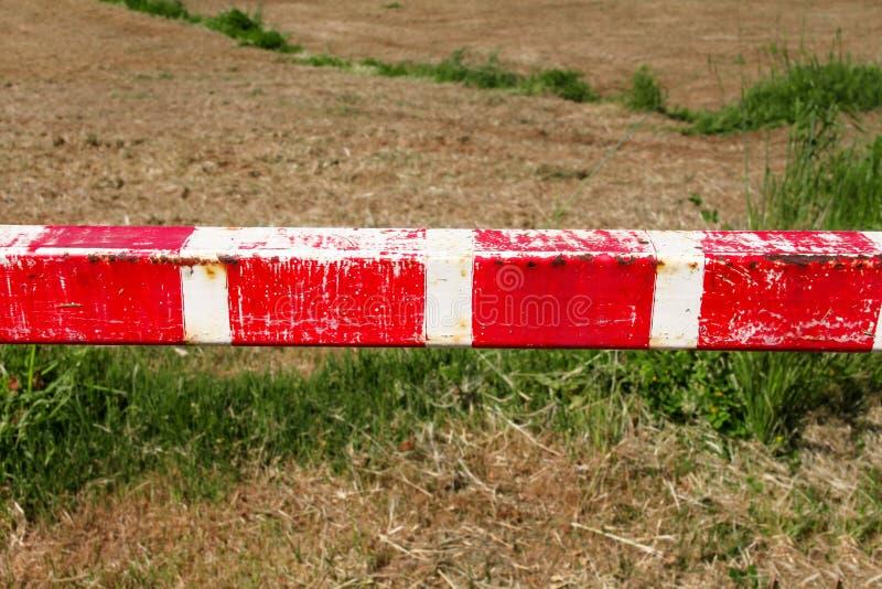 Το προειδοποιητικό σημάδι, λεπτομέρεια του κόκκινου και άσπρου εμποδίου σημαδιών στην πράσινη χλόη στη φύση, κλείνει επάνω Μεταφο στοκ φωτογραφία με δικαίωμα ελεύθερης χρήσης