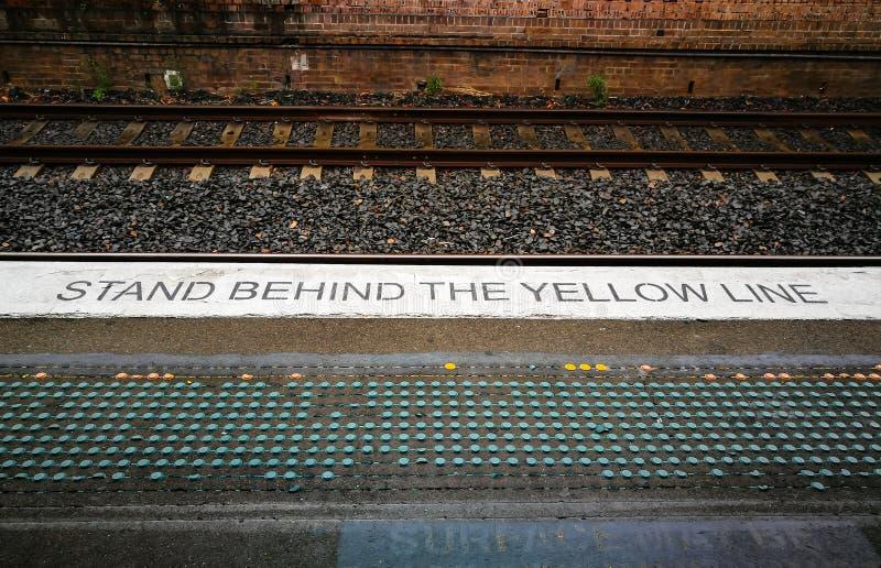 Το προειδοποιητικό σημάδι που φυτεύεται στο Μαύρο στην πλατφόρμα σιδηροδρόμων λέει τη στάση ` πίσω από την κίτρινη γραμμή ` στοκ φωτογραφία με δικαίωμα ελεύθερης χρήσης