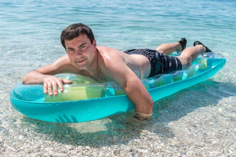 Το προκλητικό άτομο κολυμπά στη θάλασσα με το διογκώσιμο στρώμα στοκ εικόνες