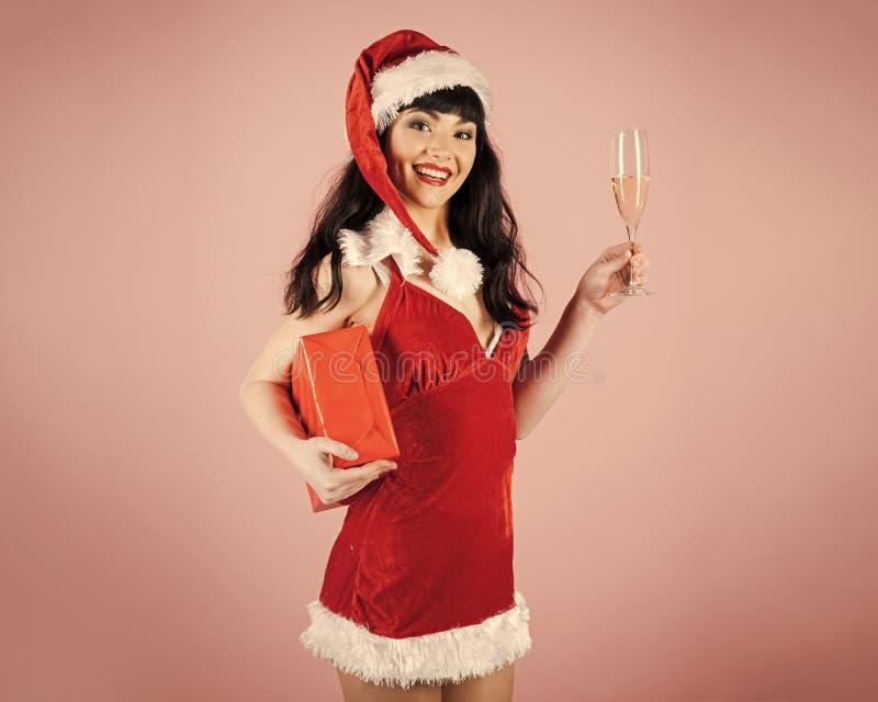 Το προκλητικό κορίτσι στο καπέλο santa κρατά το γυαλί σαμπάνιας και το κόκκινο πακέτο στοκ φωτογραφία