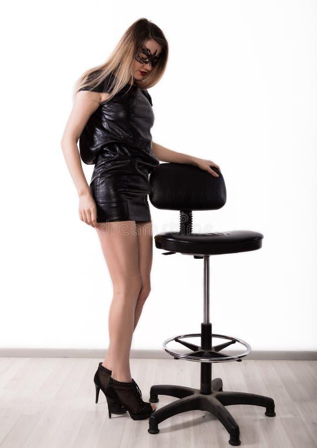 Το προκλητικό σαγηνευτικό womanin μια λίγη μαύρη μάσκα φορεμάτων και δαντελλών δέρματος χορεύει κοντά στην υψηλή καρέκλα κορίτσι  στοκ εικόνες