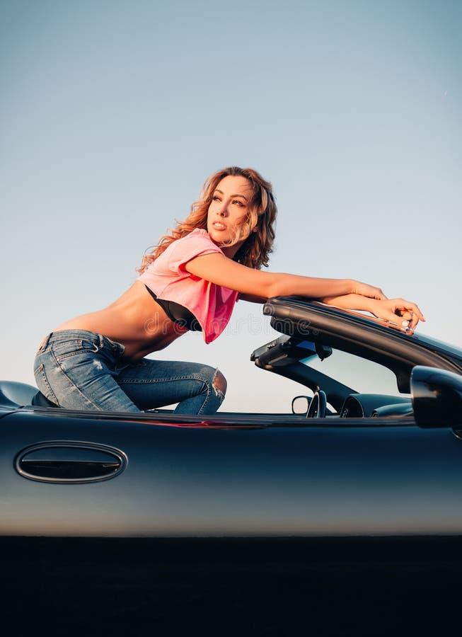 Το προκλητικό όμορφο νέο κορίτσι έντυσε στα τζιν και τη συνεδρίαση θέματος στο καμπριολέ αυτοκινήτων Υπαίθριο πορτρέτο στο ηλιοβα στοκ εικόνα με δικαίωμα ελεύθερης χρήσης