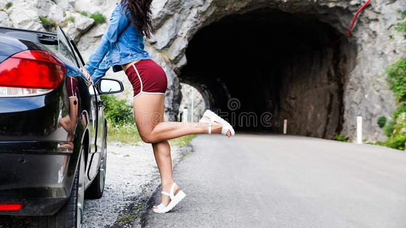 Το προκλητικό brunette στηρίζεται και τα δύο χέρια στην πόρτα του Μαύρου μετατρέψιμου Ντυμένος στα κοντά κόκκινα σορτς και το τζι στοκ εικόνες με δικαίωμα ελεύθερης χρήσης