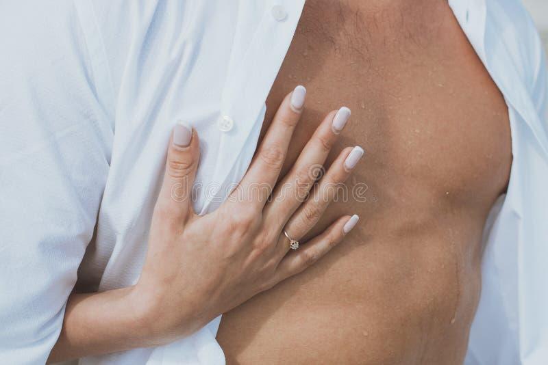 Το προκλητικά μυϊκά γυμνά άτομο και το θηλυκό δίνουν unbuckle τα τζιν του στοκ εικόνα