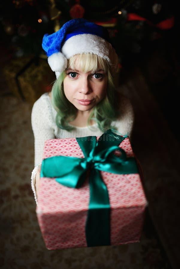 Το προκλητικό νέο κορίτσι δίνει το δώρο κάτω από το χριστουγεννιάτικο δέντρο στοκ φωτογραφία με δικαίωμα ελεύθερης χρήσης