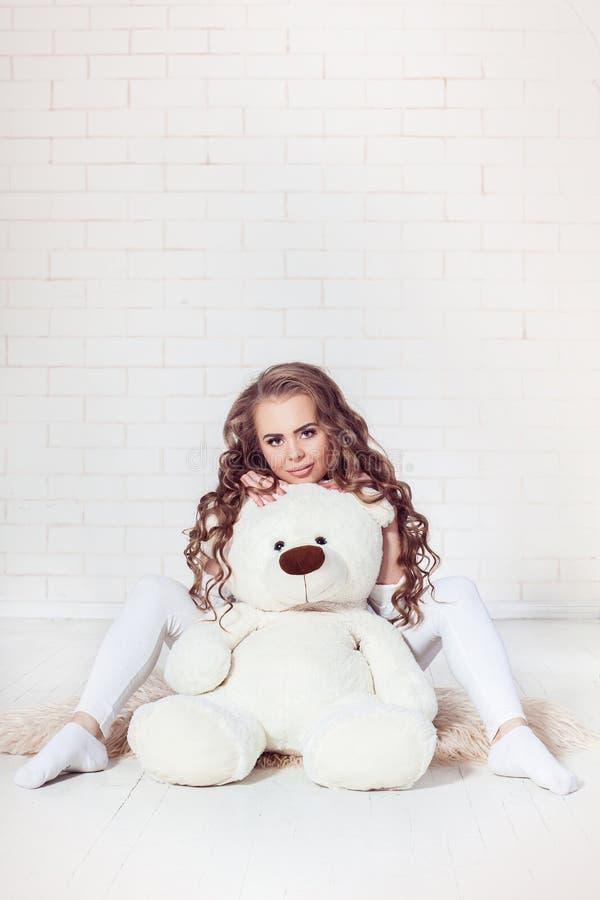 Το προκλητικό σκοτεινό ξανθό αγκάλιασμα κοριτσιών teddy αντέχει στοκ φωτογραφία με δικαίωμα ελεύθερης χρήσης
