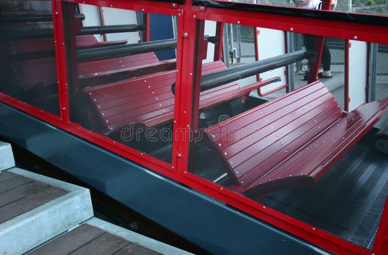 Το προς τα κάτω κατεβαίνοντας αυτοκίνητο σιδηροδρόμων με τους κόκκινους πάγκους mountainside περπάτησε την πλατφόρμα στο μπλε εθν στοκ εικόνα με δικαίωμα ελεύθερης χρήσης