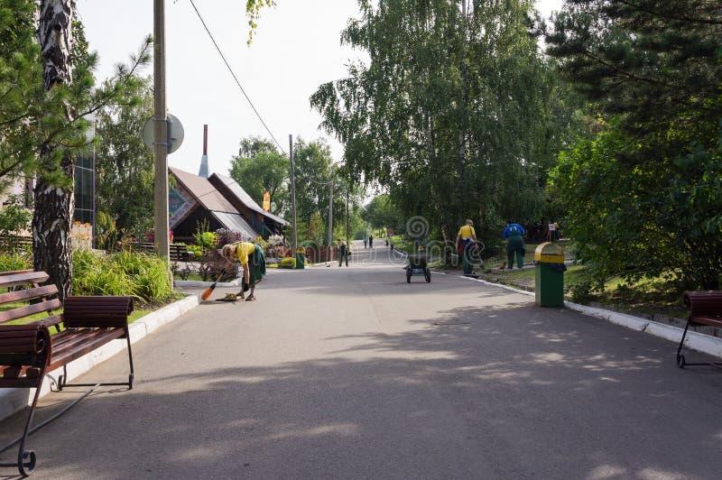 Το προσωπικό υπηρεσιών αφαιρεί τους λόγους του πάρκου στα ξημερώματα στοκ εικόνες με δικαίωμα ελεύθερης χρήσης