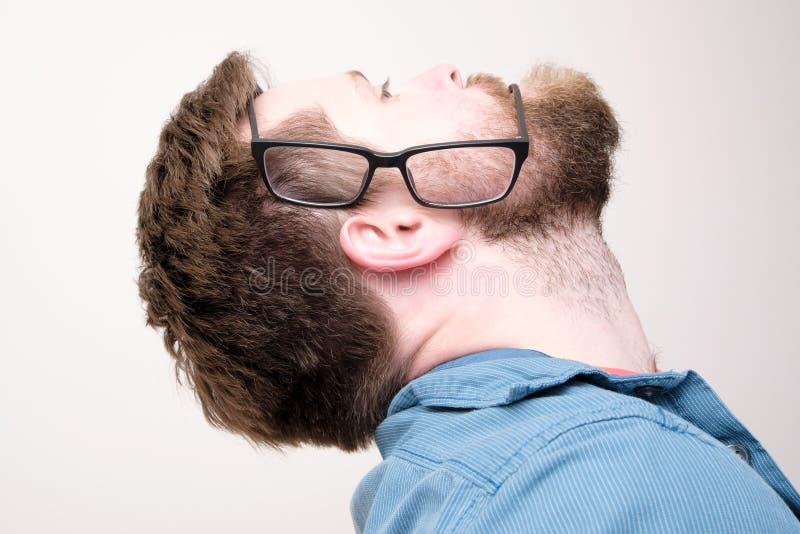 Το προφίλ ενός γενειοφόρου άντρα που βάζει γυαλιά στο πλάι και κατέληξε σαν ένα αυτί είναι στόμα Ενδιαφέρουσα, αστεία ιδέα στοκ φωτογραφία με δικαίωμα ελεύθερης χρήσης