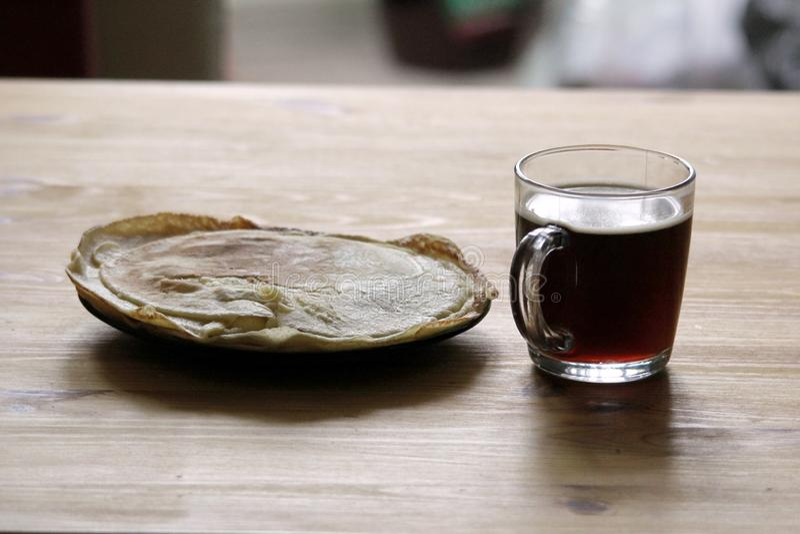Το πρωί στον πίνακα ένα φλιτζάνι του καφέ και ένα πιάτο των τηγανιτών στοκ φωτογραφία με δικαίωμα ελεύθερης χρήσης