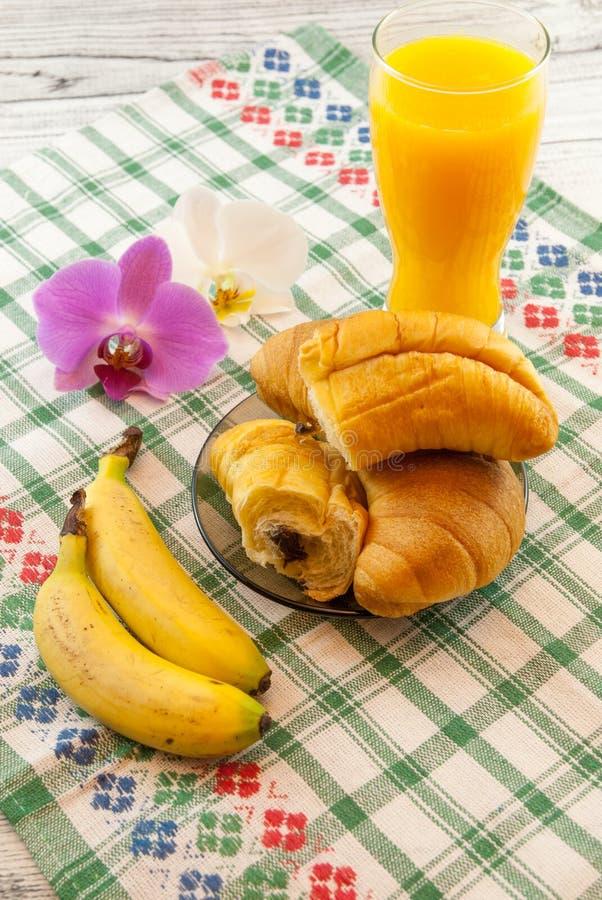 Το πρόγευμα αποτελείται από τα croissants που γεμίζουν με τις μπανάνες σοκολάτας και ο χυμός από πορτοκάλι με τη ορχιδέα προγευμα στοκ φωτογραφία