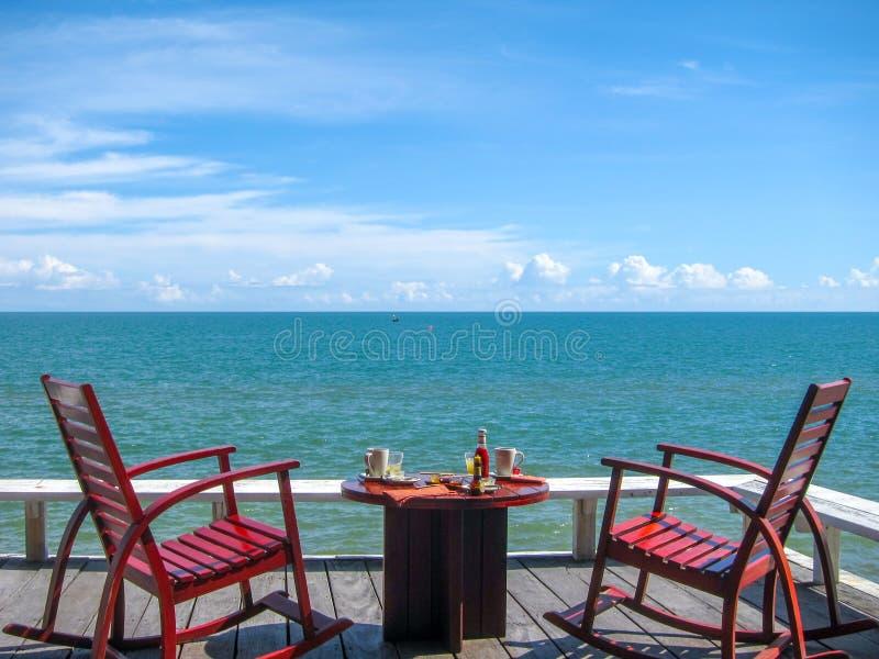 Το πρόγευμα εξυπηρετεί στο μπαλκόνι ευθεία την παραλία σε ένα beautifu στοκ φωτογραφία με δικαίωμα ελεύθερης χρήσης