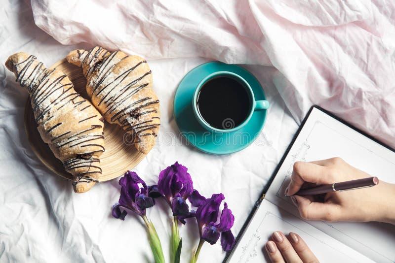 Το πρόγευμα στο κρεβάτι, ένας croissant με τον καφέ και τα λουλούδια στο κρεβάτι, παίρνουν τις σημειώσεις σε ένα σημειωματάριο στοκ εικόνες