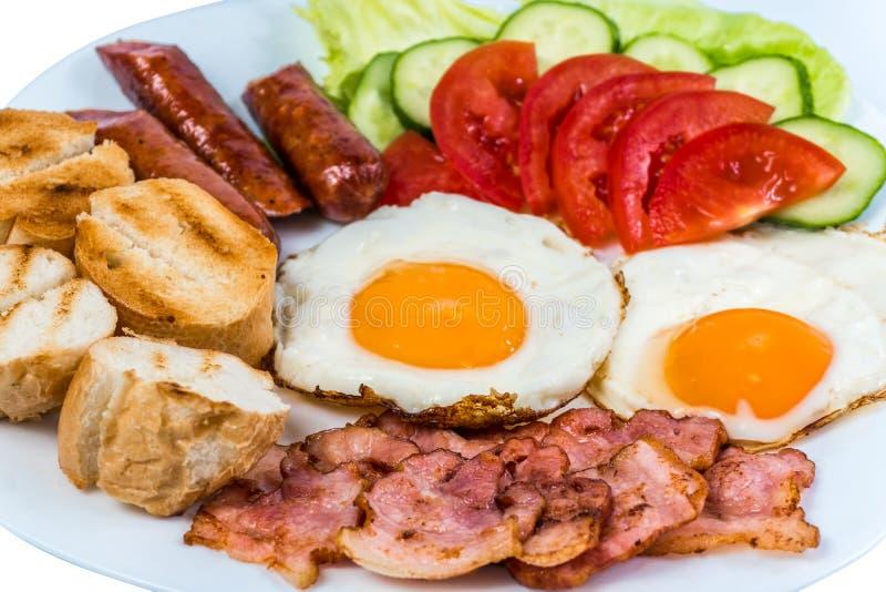 Το πρόγευμα τηγάνισε το τηγανισμένο μπέϊκον φρέσκων λαχανικών αυγών, τα τηγανισμένες λουκάνικα και τις ελιές σε ένα άσπρο πιάτο στοκ φωτογραφίες με δικαίωμα ελεύθερης χρήσης