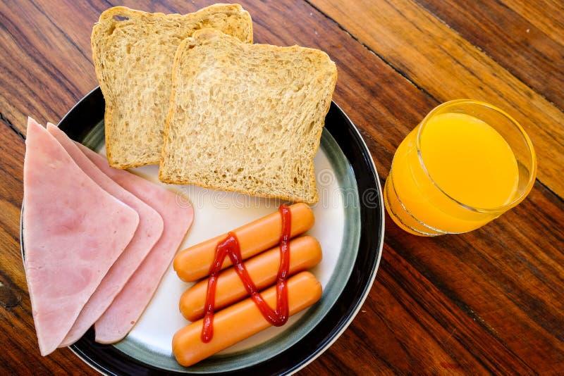Το πρόγευμα του ζαμπόν, το ποτήρι του χυμού από πορτοκάλι και η κινηματογράφηση σε πρώτο πλάνο Αμερικανός φρυγανιάς προγευματίζου στοκ φωτογραφία