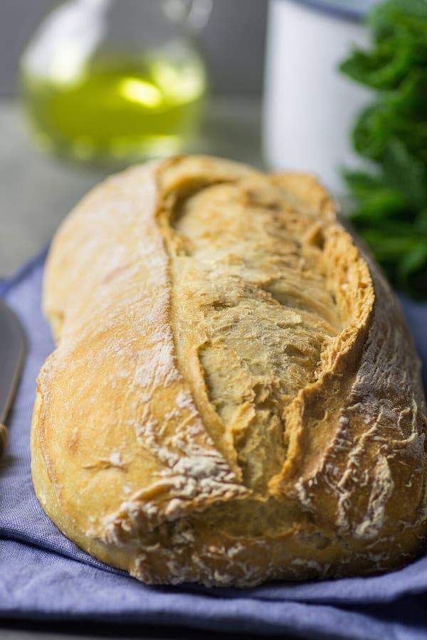 Το πρόσφατα ψημένο χέρι επεξεργάστηκε την αγροτική φραντζόλα ψωμιού στην μπλε πετσέτα λινού στο σκοτεινό κουζινών μπουκάλι χορταρ στοκ εικόνες