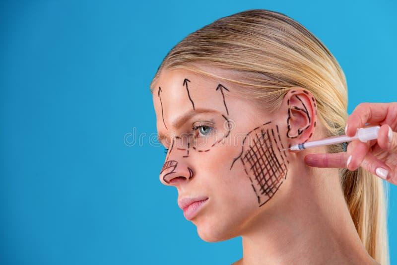 Το πρόσωπο ενός κοριτσιού με το ομαλό δέρμα χωρίς ρυτίδες κάνει τους πυροβολισμούς ομορφιάς Σύριγγα δίπλα στο πρόσωπο, σαλόνι φρο στοκ φωτογραφία με δικαίωμα ελεύθερης χρήσης